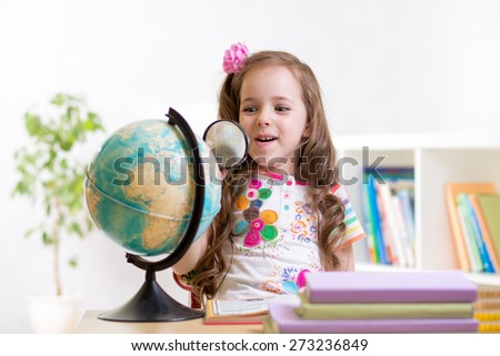 child girl reading with magnifying glass look the globe - stock photo