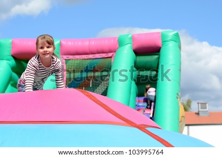 Child girl's fun on inflatable playground