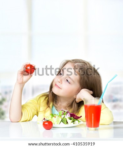 Child girl sitting at table eating fresh salad drinking juice. Female kid healthy nutrition concept background.Toddler having lunch holding tomatoes in hands. - stock photo