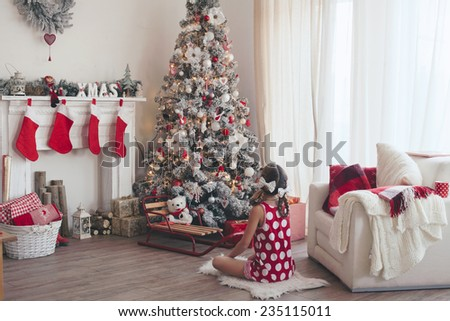 Child girl sitting near decorated Christmas tree and fireplace in beautiful hotel room in the holiday morning - stock photo