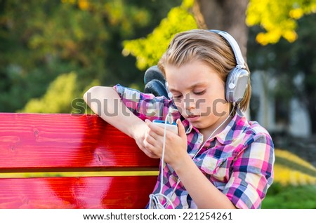Child girl sitting on a bench in the park and listening to music on headphones. - stock photo