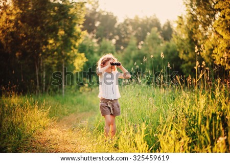 child girl watching birds with binocular on the walk in sunny summer forest - stock photo
