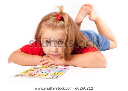 Child girl with a book on the floor - stock photo