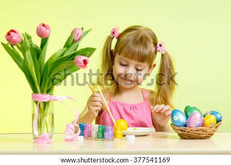 Child girl with brush coloring easter eggs - stock photo