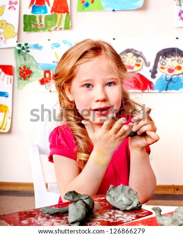 Child girl with clay in play room. Preschool. - stock photo