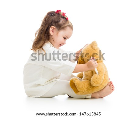 child girl with clothes of doctor playing with toy - stock photo