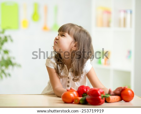 child girl with expression of disgust against vegetables - stock photo