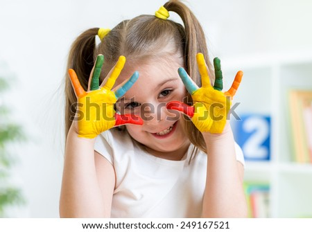 child girl with painted fingers at home - stock photo
