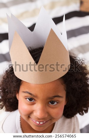 Child girl with paper crown looking . view from above