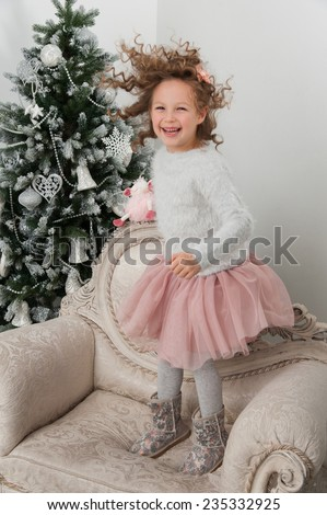 Child girl with sheep toy jump on background of Christmas tree