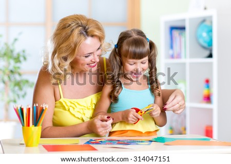 Child girl with woman cutting out scissors paper in preschool - stock photo