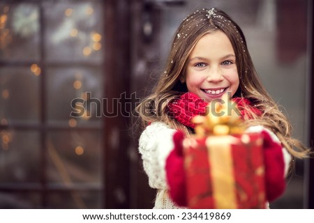 Child giving a Christmas present near her house door, snowy outside - stock photo