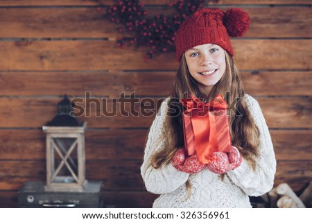Child giving a Christmas present on rustic wooden background, farmhouse interior. - stock photo