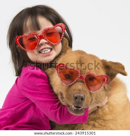 Child giving hug to dog. Both wearing heart shaped shades. - stock photo