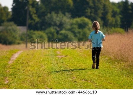 Child goes on a country road. Sunlight. - stock photo