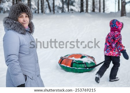 Child goes tubing with toboggan while mother looking at camera - stock photo