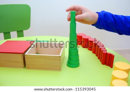 Child hand building tower made of montessori educational materials