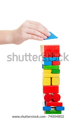 Child hand building tower made off building bricks - stock photo