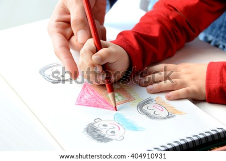 Child hand drawing with colored pencil - stock photo