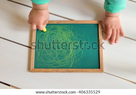 child hand drawing with crayon on the black board - stock photo