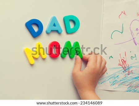 child hand forming mom and dad words with magnetic letters on refrigerator door. - stock photo