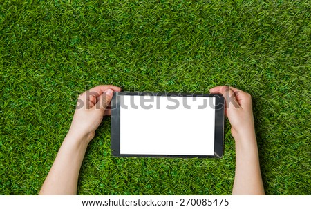 Child hand holding tablet pc. over green grass background - stock photo