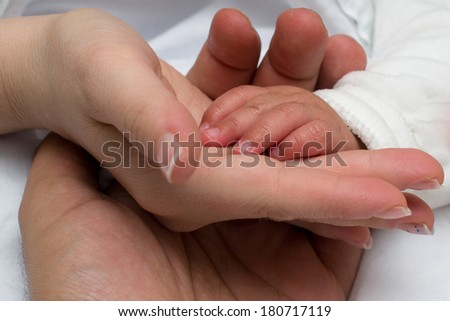 Child hand on mother and father hands