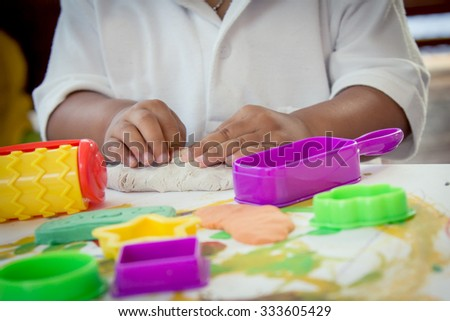 Child hand playing with clay - stock photo