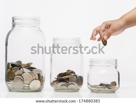 Child hand putting a coin into glass bottle, future saving concept