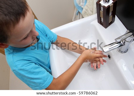Child hand washing in the washbasin - stock photo