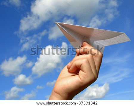child hand with paper plane against blue sky - stock photo
