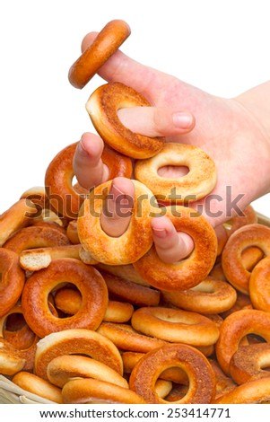 Child hand with small bagels isolated on white background - stock photo