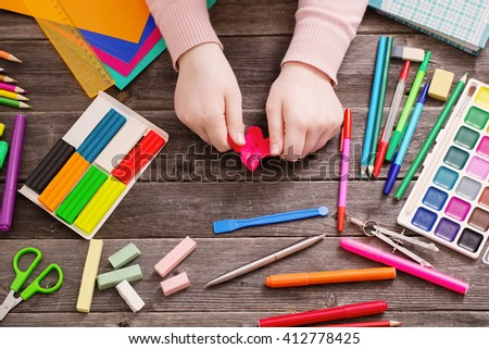 child hand withplasticine on wooden background - stock photo
