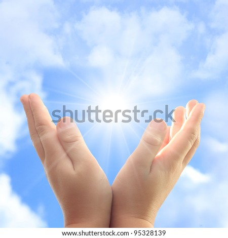 Child hands against blue sky and sun. - stock photo