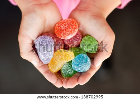 Child hands full of colorful jelly candies with sugar. Dark background - stock photo