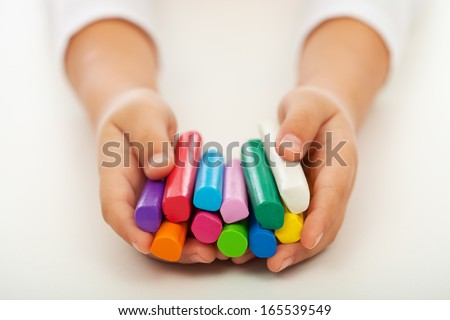 Child hands holding colorful clay bars - closeup - stock photo