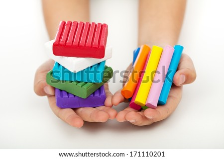 Child hands holding colorful modeling clay bars and blocks - stock photo