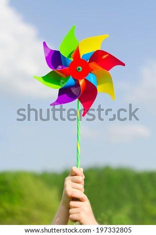 Child hands holding pinwheel against blue sky. - stock photo