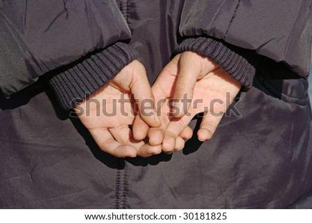 child hands in jacket on back closeup