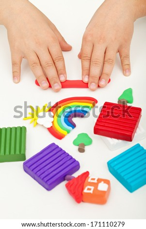 Child hands playing with colorful modeling clay - stock photo