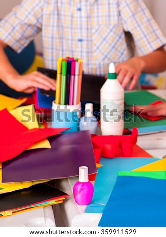 Child hands with parer and color pencils. - stock photo