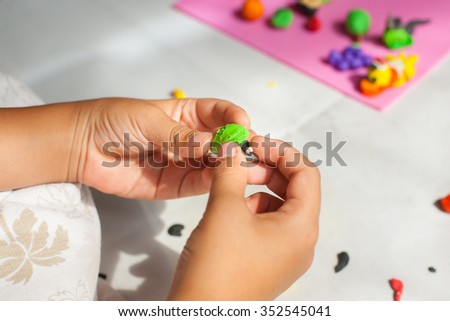 Child hands with plasticine in home at Thailand. - stock photo
