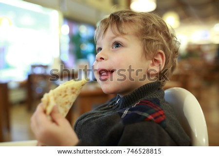 Child has pizza in highchair in cafe