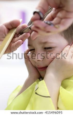 Child having a haircut at the barbershop - stock photo
