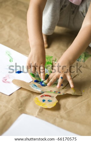 Child having fun and painting with foot feet finger - stock photo