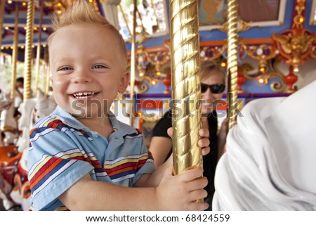 Child Having Fun on the Merry-Go-Round - stock photo