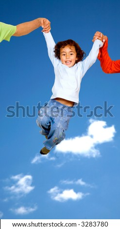 child having fun with his parents outdoors with a blue sky in the background
