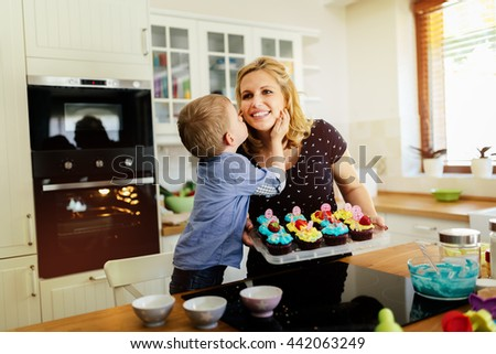 Child helping mother prepare muffins in kitchen - stock photo