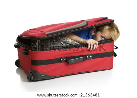 Child hiding inside a red suitcase. Isolated on a white background. - stock photo