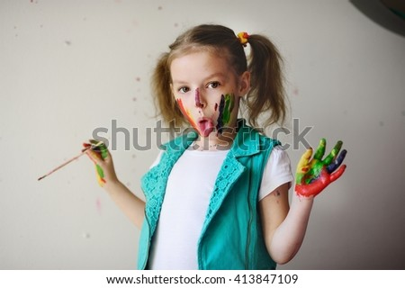 Child himself dirty in the color paint and looks into the camera. Girl has fun and painting. Children's creativity. Art for baby. Messy child's face showing tongue and holding a brush in his hand. - stock photo